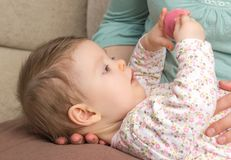 Baby playing with pacifier lying over mother legs Stock Images