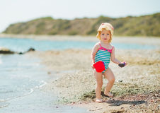 Baby playing with pail on sea shore. Baby girl playing with pail on sea shore royalty free stock photography