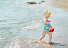 Baby playing with pail on seashore. Baby girl playing with pail on seashore stock image