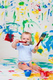Baby playing with paintbrushes royalty free stock image