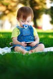 Baby is playing with phone on the green grass Stock Photography