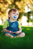 Baby is playing with phone in the park Stock Images
