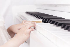 Baby playing on piano. Little biautiful girl  playing on white piano unfocussed background Royalty Free Stock Image