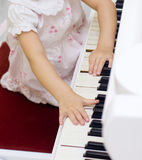 Baby playing on piano. Little biautiful girl playing on white piano unfocussed background Stock Photos