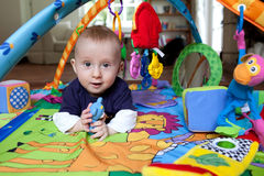 Baby playing on playmat Stock Images