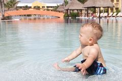 Baby Playing in Pool. Baby playing and splashing in a tropical resort pool Royalty Free Stock Photo