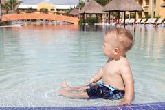 Baby Playing in Pool. Baby playing and splashing in a tropical resort pool Royalty Free Stock Photos