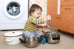 Baby playing with pots. 1 year baby with pots Stock Images