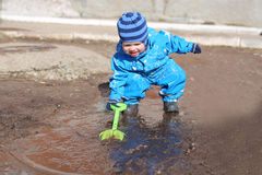 Baby playing in puddle. 18 months baby playing in puddle Stock Photography