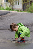 Baby playing in puddles Stock Images