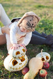 Baby playing with pumpkins Stock Image