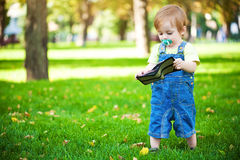 Baby playing with a purse in the green park Royalty Free Stock Photos