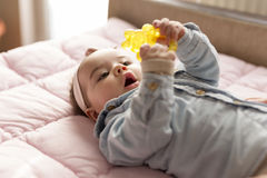 Baby playing with a rattle Royalty Free Stock Images