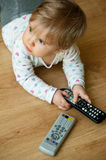 Baby playing with remote. Closeup of a baby girl, playing with an electronic remote controller Royalty Free Stock Images