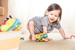 Baby Playing on Rug. Baby playing and crawling around, making faces, on a rug on the floor Stock Image