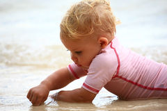 Baby playing in the sand. With her fingers Royalty Free Stock Images