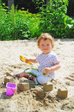 Baby playing on the sand Stock Image