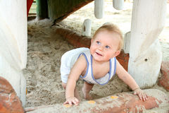 Baby playing in sand. A smiling male baby crawling through some sand stock images