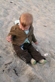 Baby playing in sand. A baby boy or toddler, sitting and playing in sand Royalty Free Stock Images