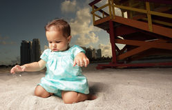 Baby playing with the sand. Young baby on the beach playing with the sand Royalty Free Stock Images