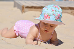 Baby playing in the sand Stock Photography