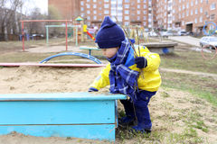 Baby playing with sand on playground in spring. 18 months baby playing with sand on playground in spring Royalty Free Stock Photo