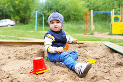 Baby playing with sand on playground in summer. 21 months baby playing with sand on playground in summer Royalty Free Stock Image