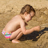 Baby playing in sand. On the river beach Royalty Free Stock Photo