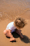 Baby playing with sand by the sea. Baby playing with sand on the surf edge by the sea, on the beach Royalty Free Stock Image
