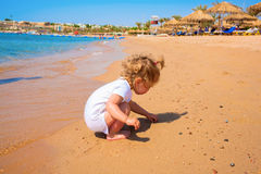 Baby playing with sand by the sea. Baby playing with sand on the surf edge by the sea, on the beach Royalty Free Stock Photography