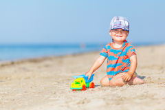 Baby playing on the sandy beach Stock Images