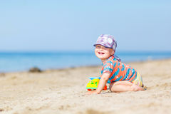 Baby playing on the sandy beach Stock Photo