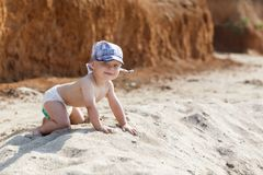 Baby playing on the sandy beach Royalty Free Stock Images