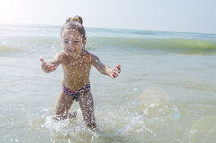 Baby playing with sea water on the beach Royalty Free Stock Image