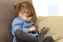 Baby playing with a smart phone at home Royalty Free Stock Photography