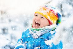 Baby playing with snow in winter. Child in snowy park. Royalty Free Stock Photos