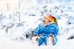 Baby playing with snow in winter. Child in snowy park. Stock Photography