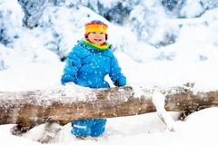 Baby playing with snow in winter. Child in snowy park. Stock Images