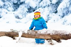 Baby playing with snow in winter. Child in snowy park. Stock Image