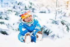Baby playing with snow in winter. Child in snowy park. Stock Photo