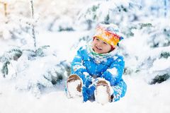 Baby playing with snow in winter. Child in snowy park. Stock Photos