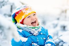Baby playing with snow in winter. Child in snowy park. Royalty Free Stock Images