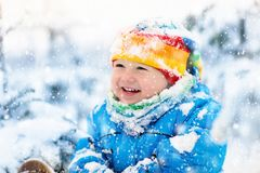 Baby playing with snow in winter. Child in snowy park. Baby playing with snow in winter. Little toddler boy in blue jacket and colorful hat catching snowflakes Stock Photos