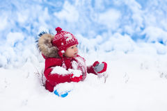 Baby playing with snow in winter. Stock Image
