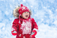 Baby playing with snow in winter. Royalty Free Stock Images