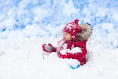 Baby playing with snow in winter. Royalty Free Stock Photography