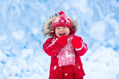Baby playing with snow in winter. Stock Photography