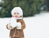 Baby playing with snow in winter park Royalty Free Stock Photo
