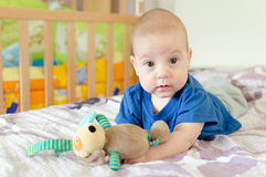 baby playing with soft toy on the bed Royalty Free Stock Image