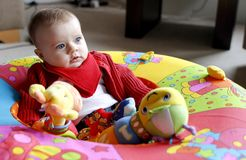 Baby playing with soft toy in playpen. Cute baby girl playing with large soft toy in home stock image